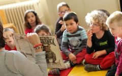 Woman reading a book to children