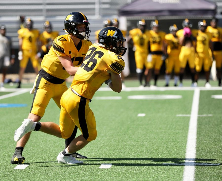 WLU QB Jamie Diven hands off the ball to WLU RB Tyler Moler. Photo from WLU Sports Information Office.