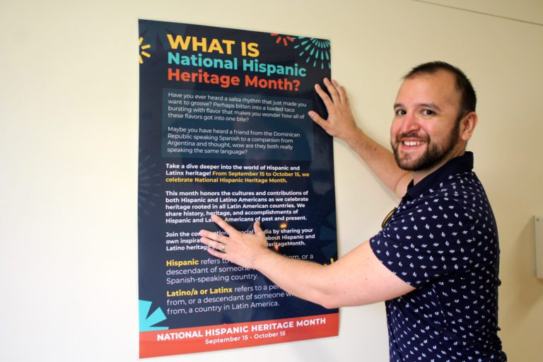Dr. Felipe Rojas places a poster in the Elbin Library hallway proclaiming Sept. 15 – Oct. 15 Hispanic Heritage Month on the Hilltop.