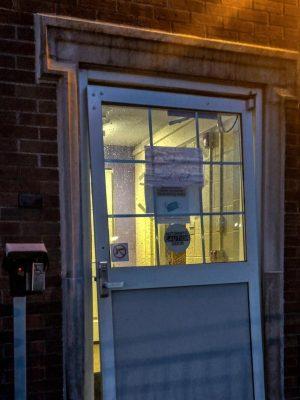 Broken door to get into Hughes Hall represents the broken vistor policy due to COVID-19. Like the broken door, the policy is an inconvenience students.