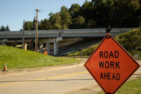 A road work sign below the I-70 bridge.