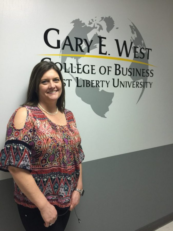 Christine DeWitt standing in the Gary E. West College of Business wing located on the second floor of Main Hall.