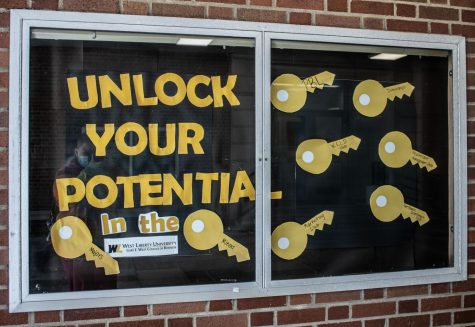 A College of Business motivational poster located on the outside of Main Hall.
